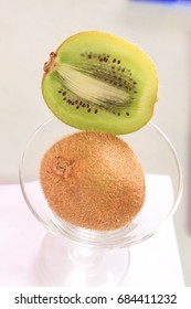 One kiwi fruit sliced ??in half on a white background.