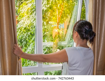 one lady open curtain at window