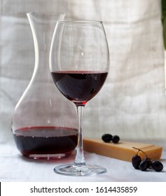 One large glass of red wine, a decanter of wine, a piece of Parmesan cheese and some dark grapes on a background of white linen curtain