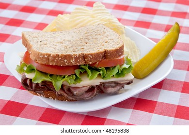 one large roast beef sandwich on oat bread with tomatoes and lettuce on a plate with classic red and white checkered tablecloth