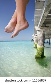 One of a large series. Great set of legs hanging over the edge of a tropical jetty.