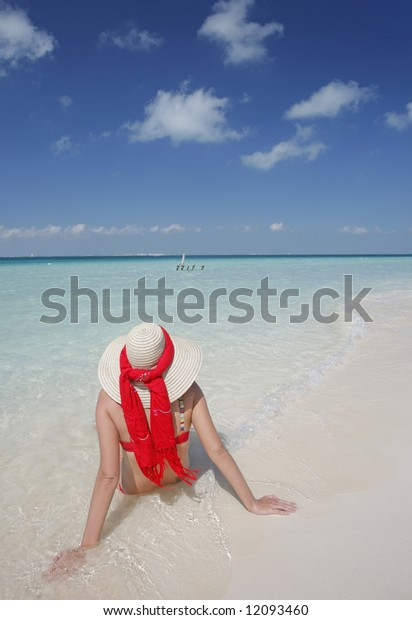 One of a large series. Woman in straw hat sunbathing by the water's edge on a tropical beach.