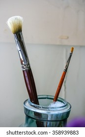 One large and small clean paint brushes in jar waiting to be used in an artist's studio.