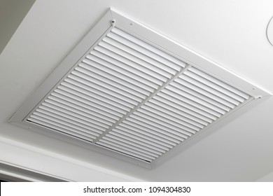 One large white painted metal furnace air vent grill with many openings on a ceiling close-up. Square outflow air filter door vent in a modern home ceiling up close.