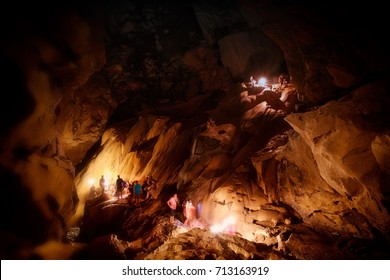 One of the largest and most visited caves in Asia with smeared silhouettes of travelers people walking through the main cave center