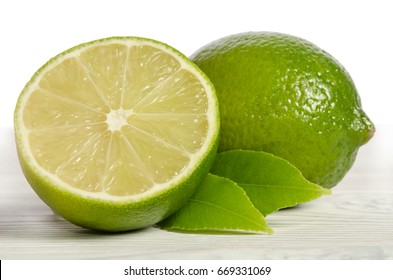 one lemon with half of  juicy lime on a wooden table