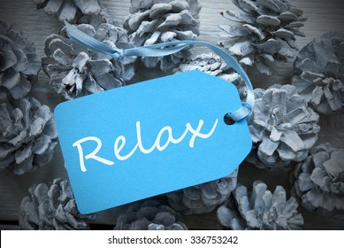 One Light Blue Label On Fir Cones And White Wooden Background. English Text Relax Vintage Or Retro Style Used As Winter Or Christmas Background With Frame