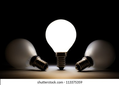 One light bulb shining in a dark space with other dead light bulbs, close up