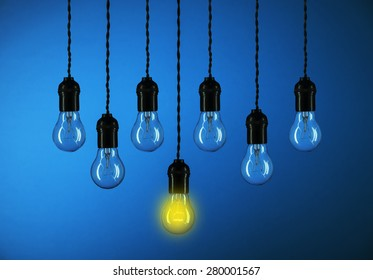 One light bulbs with glowing one isolated over blue background-leadership concept