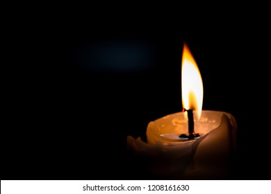 One light candle burning brightly in the black background.
