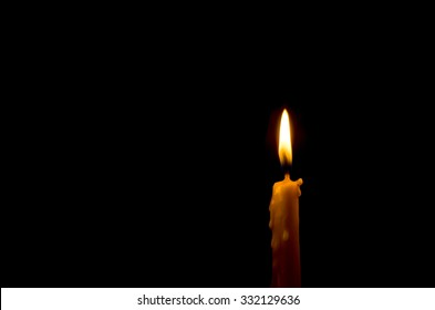 One light candle burning brightly in the black background