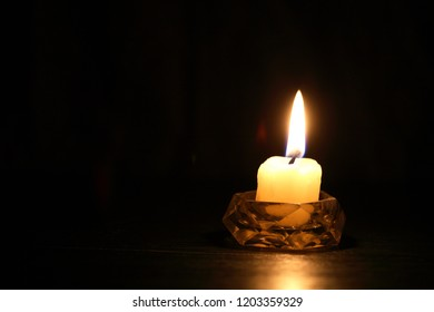One lighting candle in candlestick against dark background