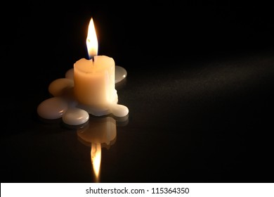 One lighting candle on dark background with free space for text