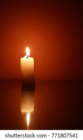 One lighting candle with reflection against dark background