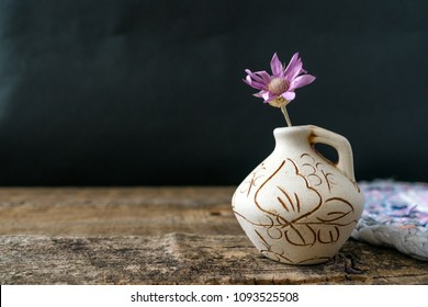 One lilac flower Xeranthemum on clay vase on wooden texture background close up. Wabi Sabi, Hygge, Lagom style. Loneliness, simplicity, minimalism concept. Copy space