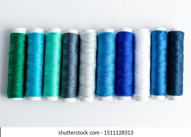One line of colourful blue spools of thread displayed horizontally, isolated on white, top view
