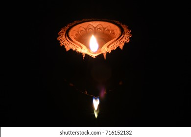 One lit clay diya (lamp) placed on a black background.