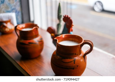 One litre pottery cup filled with alcoholic Pulque made from the Agave plant at a Mexican Cantina in Mexico.