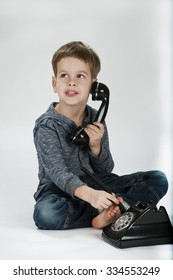 One little boy posing in studio with telephone