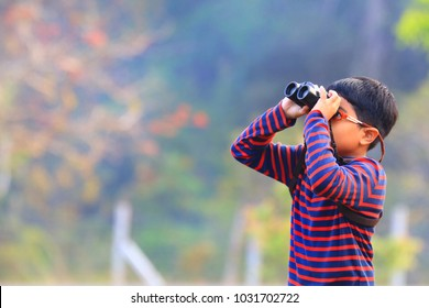 One little boy use binoculars watching bird in nature with blurry background.