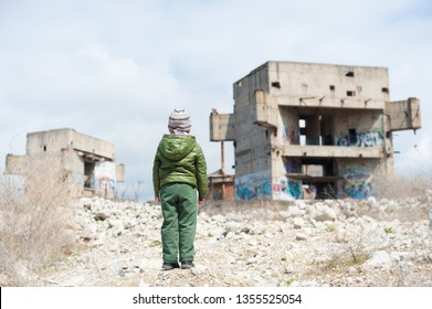 one little child in green jacket standing on ruins of destroyed buildings in war zone