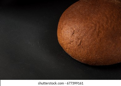 one loaf of bread close-up on a dark background
