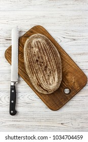 one loaf of bread on a cutting board with knife.