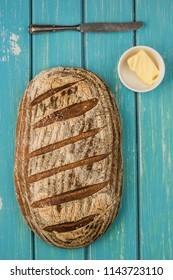 One loaf of sourdough bread on blue bable board