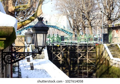 One of the locks of the Canal Saint Martin in Paris by winter, under a white cover of fresh snow.