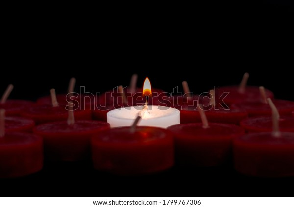one lone lit white candle with flame surrounded by red unlit candles and standing out