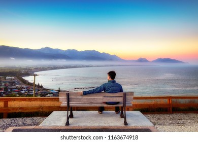 One lonely young man sits on a bench on the top of a hill. The view is breathtaking. There are sunshine, colorful sky, town and coastline and ocean. He is deep thinking and contemplating in his mind.