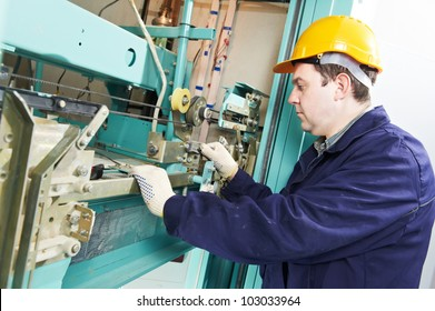 One machinist worker at work adjusting elevator mechanism of lift with spanner