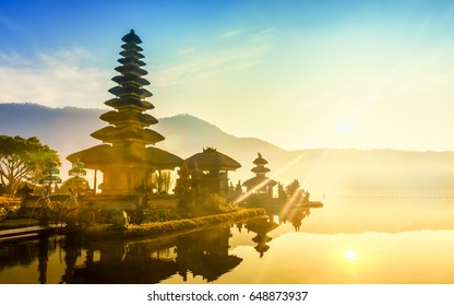 One of the main popular attractions of tropical island Bali visited daily by hundreds of tourists from around the world for look amazing scenic view, hindu temple on Bratan lake at sunrise / Indonesia