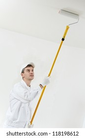 One male house painter worker painting and priming ceiling with painting roller