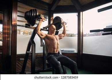one man, 30-39 years, bodybuilder exercising overhead plate press machine. At home (with many windows) in his own gym with professional fitness equipment.