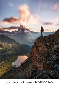 one man / adventurer standing on a cliff overlooking the matterhorn of zermatt switzerland, sunset light and long exposure clouds over the famous peak, reflections on lake in the valley