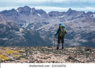 One man backpacker stands in front of mountains of Patagonia