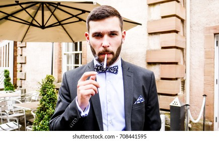 One man with a beard and a smart suit with bow tie standing and smoking a cigarette, outside an old building.