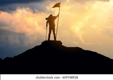 One man caught the flag. He is on top of a hill , sunset sky