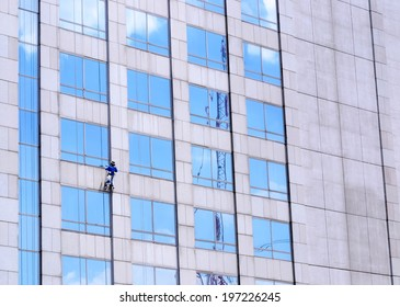 one man cleaning windows on a big building