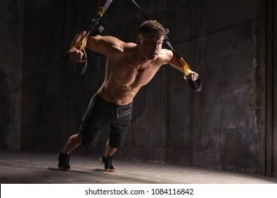 One man exercising suspension training trx on dark studio
