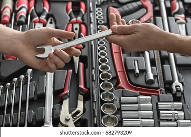 One man gives another a spanner above the dark toolbox in the workshop. In the toolbox there are black-red pliers and screwdrivers, spanners, saw and different nozzles. Closeup. Horizontal.