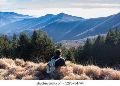 One man hiker wearing vintage rucksack sitting alone admiring the mountain landscape in winter.