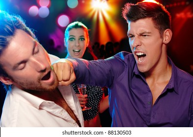 One man hitting another on the face in nightclub, woman watching from background.?