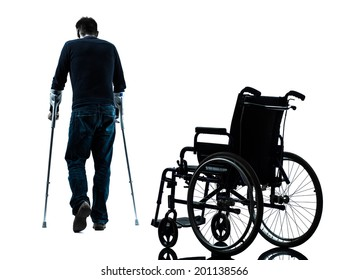 one man injured man walking with crutches in silhouette studio on white background