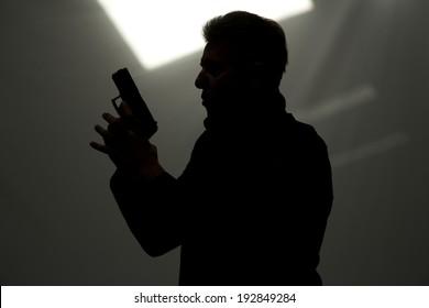 One man killer policeman aiming gun silhouette studio grey background