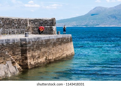One man on an old stone pier on a sunny day, with turquoise oceans and mountains in the background. Taken in Renvyle along the Wild Atlantic Way in Ireland.