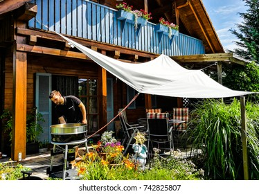 One man outside a wooden German home, preparing a barbecue in a garden on a sunny day.