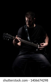 one man, playing guitar, dark and moody rock musician. Shot on black background behind.