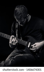 one man, playing guitar, dark and moody rock musician. Shot on black background behind. Black and white image.